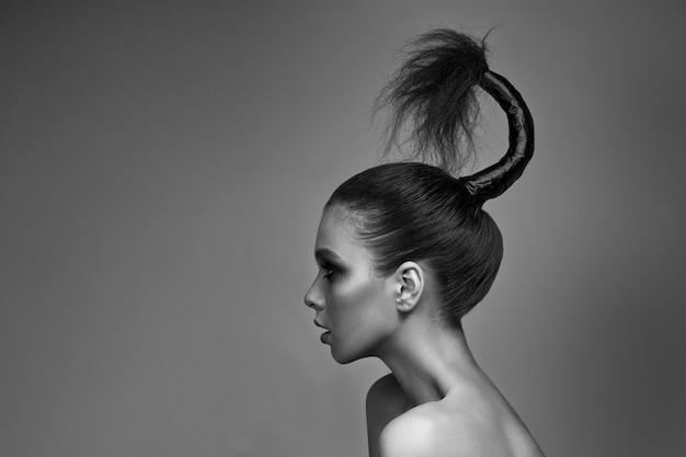Una giovane ragazza con il trucco luminoso e la pelle radiosa. acconciatura creativa sulla testa. su un grigio.