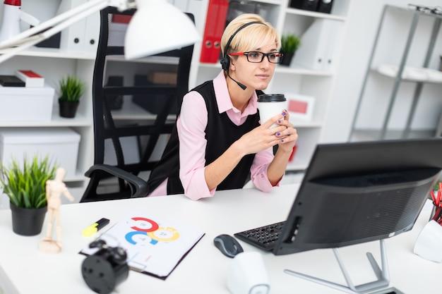 Una giovane ragazza con le cuffie seduto al tavolo del computer e in possesso di un bicchiere di caffè.