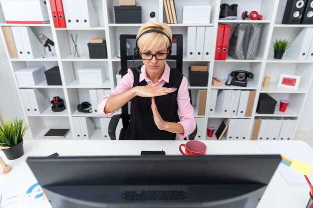 Una giovane ragazza con le cuffie seduto al tavolo del computer e mostra i palmi del segno.