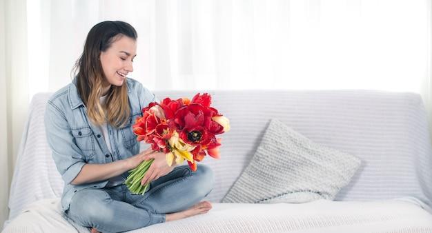 Una giovane ragazza con un grande mazzo di tulipani seduta sul divano del soggiorno.