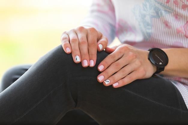 Una giovane ragazza con una bella manicure bianca tiene una valigetta nera. stile di moda