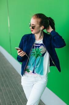 Una giovane ragazza con una giacca blu e pantaloni bianchi è in piedi all'aperto vicino al muro verde con una linea bianca verso il basso. la ragazza indossa occhiali da sole con cuori. sta alleggerendo la musica con l'aiuto delle cuffie.