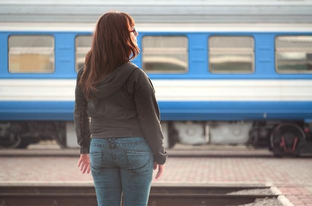Una giovane ragazza dai capelli rossi è in piedi sulla piattaforma della ferrovia e guarda il treno in partenza