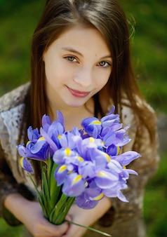 Una giovane ragazza dai grandi occhi belli tiene in mano un sorriso di fiori di iris viola primaverili. focalizzazione morbida.