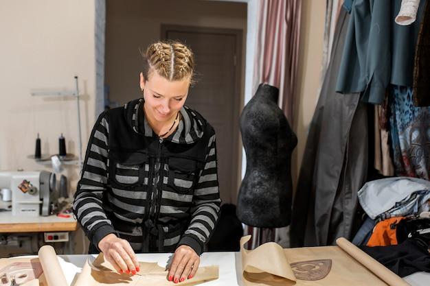 Una giovane ragazza designer abiti piegati la carta per un modello. fare vestiti su ordinazione, concetto di stilista