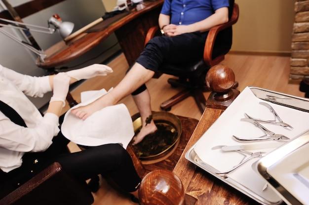 Una giovane ragazza fa un pedicure uomo sulla superficie di un salone di bellezza. cura delle unghie