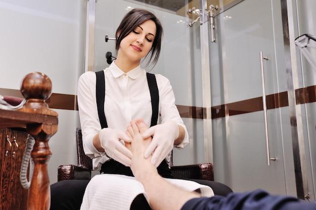 Una giovane ragazza fa un pedicure uomo sullo sfondo di un salone di bellezza.