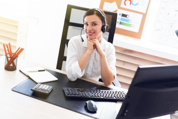 Una giovane ragazza in cuffia con un microfono seduto al tavolo di un computer.