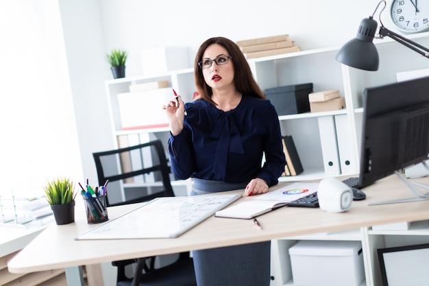 Una giovane ragazza in piedi al tavolo di un computer e lavora con una lavagna magnetica.
