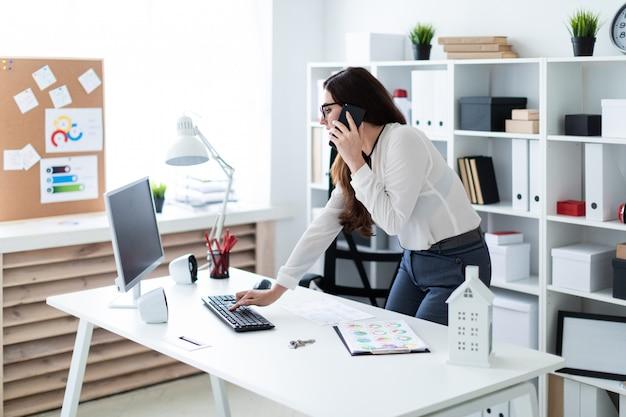 Una giovane ragazza in piedi vicino al tavolo, digitando sulla tastiera e parlando al telefono.