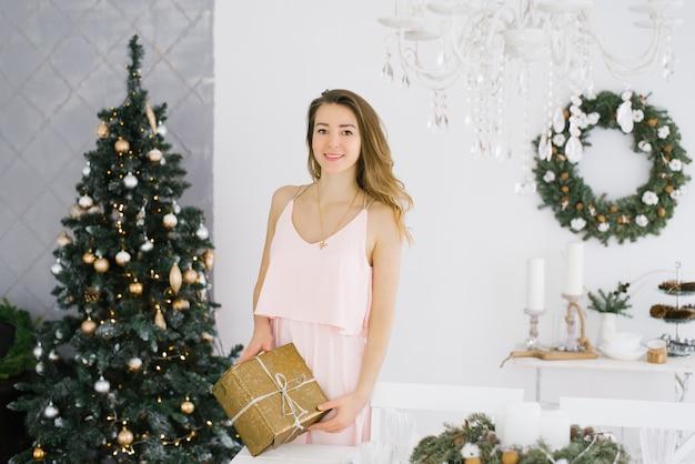 Una giovane ragazza in un bellissimo vestito rosa tiene in mano una confezione regalo d'oro con un fiocco in mano