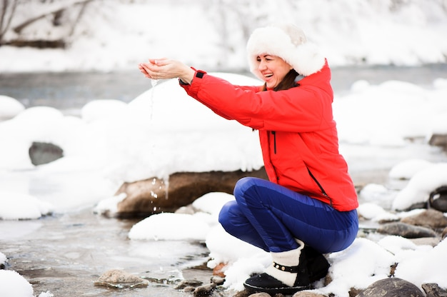 Una giovane ragazza in un parco d'inverno in una passeggiata. vacanze di natale nella foresta invernale vicino al fiume.