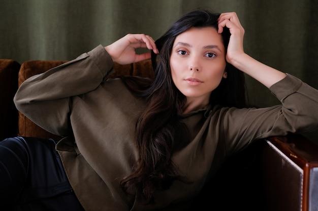 Una giovane ragazza o modella fotogenica del portafoglio è sdraiata sul divano guardando la telecamera con uno sguardo calmo.