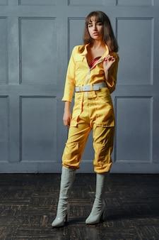 Una giovane ragazza seduttrice in un giallo vestiti sbottonati
