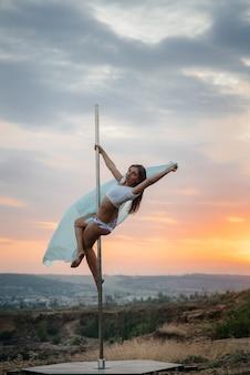 Una giovane ragazza sexy esegue incredibili esercizi in pole durante un tramonto. danza. sessualità.