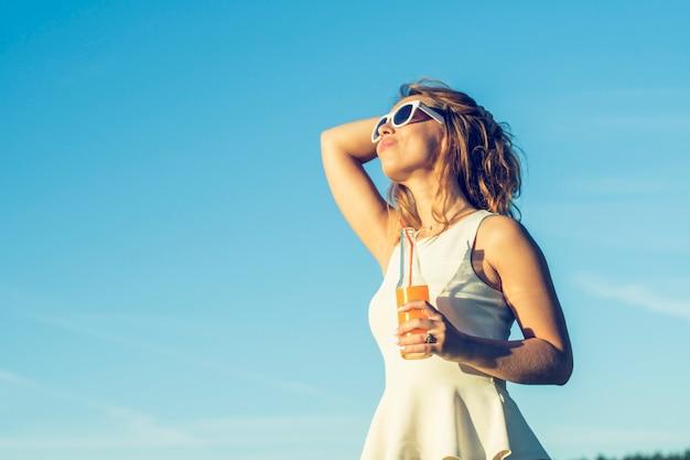 Una giovane ragazza snella con gli occhiali con i capelli ricci sorride e beve un cocktail alcolico o analcolico attraverso una cannuccia da una bottiglia in una giornata di sole estivo guardando avanti