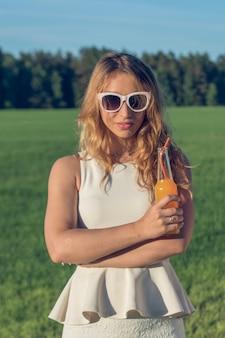 Una giovane ragazza snella con gli occhiali con i capelli ricci sorride e beve un cocktail alcolico o analcolico attraverso una cannuccia da una bottiglia in una soleggiata giornata estiva e sorride