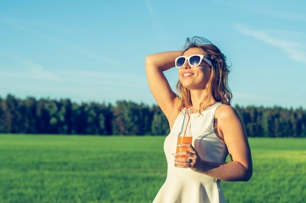 Una giovane ragazza snella con gli occhiali con i capelli ricci sorride e beve un cocktail alcolico o analcolico attraverso una cannuccia da una bottiglia in una soleggiata giornata estiva sognando