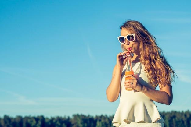 Una giovane ragazza snella con gli occhiali con i capelli ricci sorride e beve un cocktail alcolico o analcolico attraverso una cannuccia da una bottiglia in una soleggiata giornata estiva