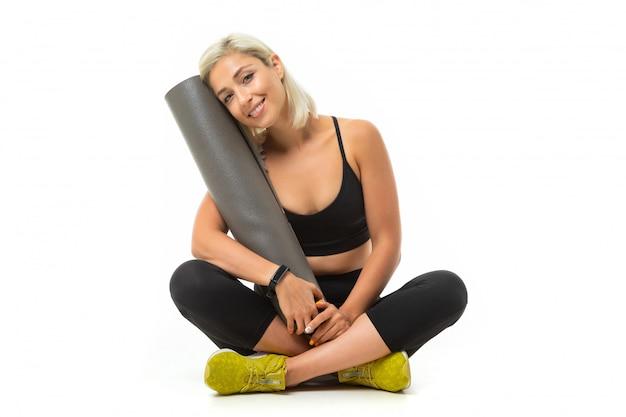 Una giovane ragazza sportiva con i capelli biondi e la manicure brillante in un top sportivo nero, leggings e scarpe da ginnastica gialle tiene in mano un tappetino sportivo.