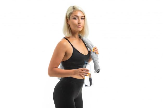 Una giovane ragazza sportiva con i capelli biondi in un'ascia sportiva e leggings neri tiene un asciugamano blu e una bottiglia d'acqua.