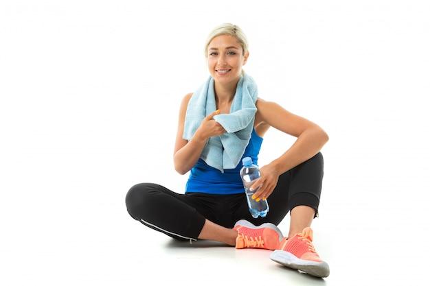 Una giovane ragazza sportiva con i capelli biondi in un'ascia sportiva nera, leggings neri e scarpe da ginnastica luminose con un asciugamano intorno al collo e una bottiglia d'acqua stanca dopo l'allenamento.