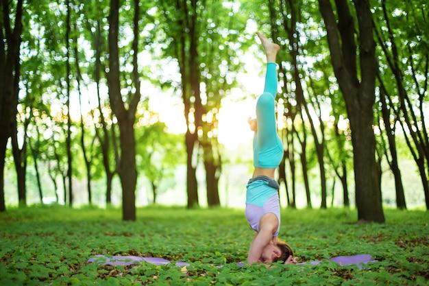 Una giovane ragazza sportiva pratica yoga in una foresta estiva verde chiusa, yoga assans postura. meditazione e unità con la natura