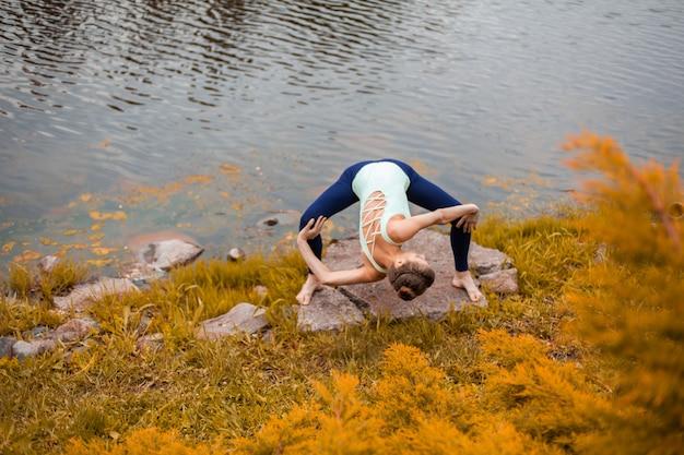 Una giovane ragazza sportiva pratica yoga su un prato giallo in autunno vicino al fiume, usa yoga assans postura.