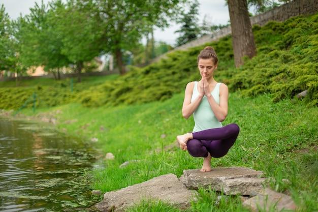 Una giovane ragazza sportiva pratica yoga su un prato verde vicino al fiume, assans postura.