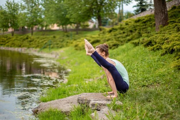 Una giovane ragazza sportiva pratica yoga su un prato verde vicino al fiume, yoga assans postura. meditazione e unità con la natura
