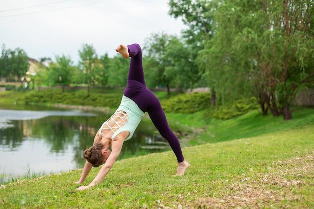 Una giovane ragazza sportiva pratica yoga su un prato verde vicino al fiume, yoga assans postura.