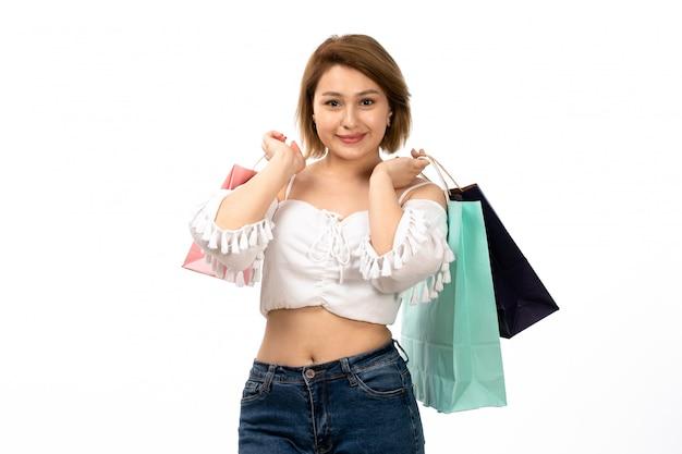 Una giovane signora attraente di vista frontale in camicia bianca e blue jeans che tengono i pacchetti di acquisto sul bianco