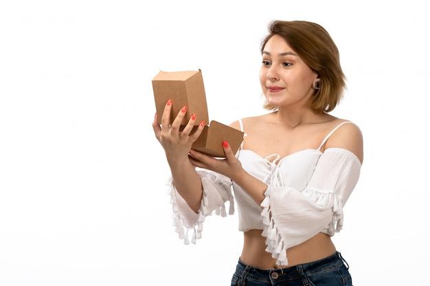 Una giovane signora attraente di vista frontale in camicia bianca e blue jeans che tengono pacchetto marrone aprendolo felice sul bianco