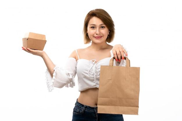 Una giovane signora attraente di vista frontale in camicia bianca e blue jeans che tengono pacchetto marrone e piccola scatola felici sul bianco