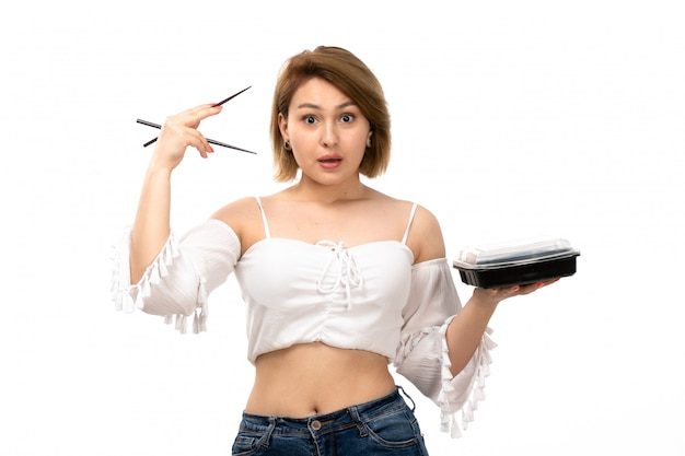 Una giovane signora attraente di vista frontale in camicia e blue jeans bianche che tengono i bastoni e la ciotola con il pasto sul bianco