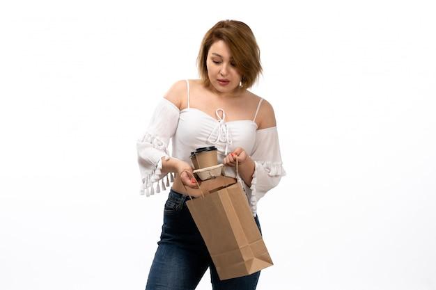 Una giovane signora attraente di vista frontale in camicia e blue jeans bianche che tengono pacchetto con caffè sul bianco