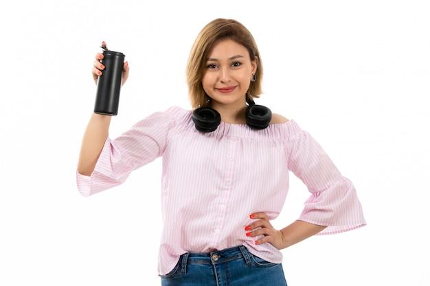 Una giovane signora attraente di vista frontale in camicia e blue jeans rosa con le cuffie nere che beve tenendo termos nero che sorride sul bianco