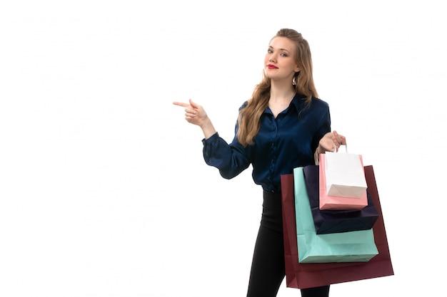 Una giovane signora attraente di vista frontale in pantaloni neri della blusa blu che posano i pacchetti di acquisto della tenuta sui vestiti bianchi di modo del fondo bianco