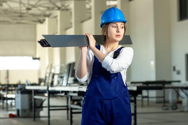 Una giovane signora attraente di vista frontale in vestito blu della costruzione e casco che lavorano tenendo dettaglio metallico pesante durante la costruzione di architettura di giorno delle costruzioni