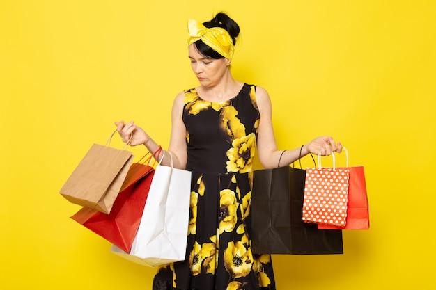 Una giovane signora attraente di vista frontale in vestito progettato fiore giallo-nero con la fasciatura gialla sulla testa che posa i pacchetti di acquisto della tenuta sul giallo
