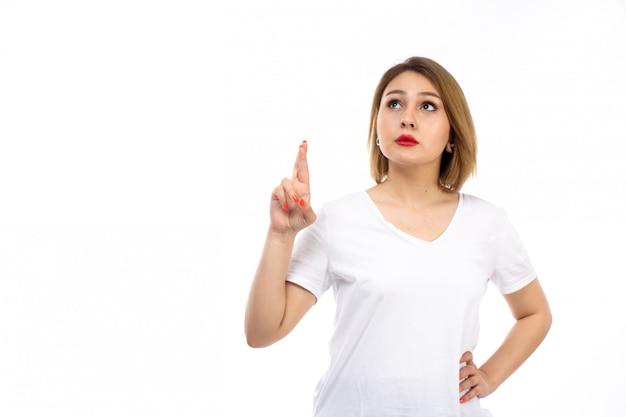 Una giovane signora di vista frontale in camicia bianca che posa pensiero sul bianco