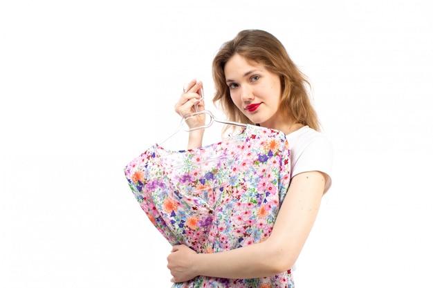 Una giovane signora di vista frontale in camicia bianca e pantaloni neri che tengono la camicia della camicetta progettata fiore sul bianco