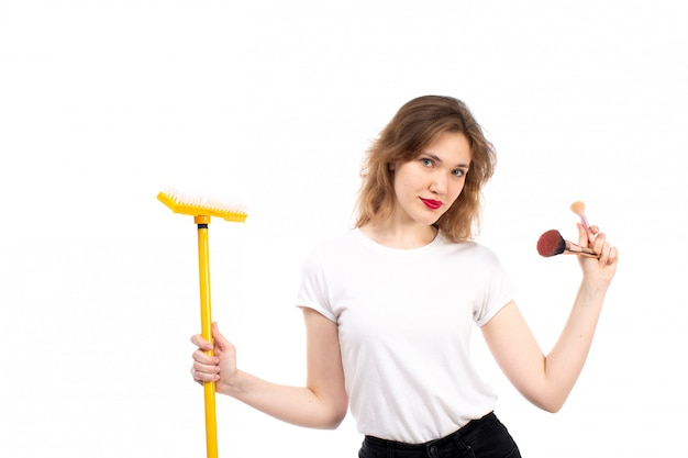 Una giovane signora di vista frontale in camicia bianca e pantaloni neri che tengono le cose gialle di trucco e di zazzera sul bianco