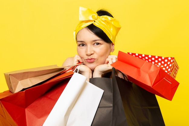 Una giovane signora di vista frontale in fiore giallo-nero ha progettato il vestito con la fasciatura gialla sulla testa che posa i pacchetti di acquisto della tenuta sul giallo