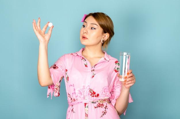 Una giovane signora di vista frontale in fiore progettato rosa pillola della tenuta del vestito e bicchiere d'acqua sull'azzurro