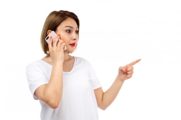 Una giovane signora di vista frontale in maglietta bianca che posa conversazione sul telefono sul bianco