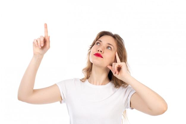 Una giovane signora di vista frontale in maglietta bianca che posa esaminando i cieli che pensano sul bianco