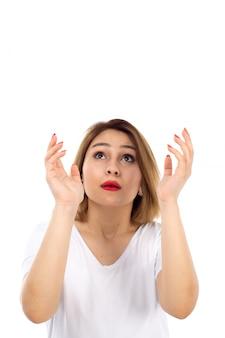 Una giovane signora di vista frontale in maglietta bianca che posa esaminando i cieli sul bianco