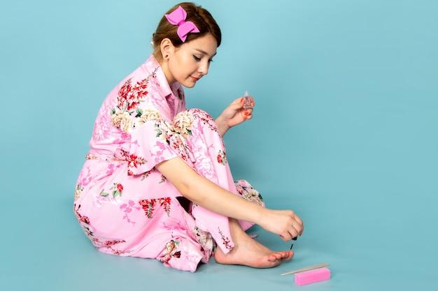 Una giovane signora di vista frontale in vestito dentellare progettato fiore che dipinge le sue unghie sull'azzurro