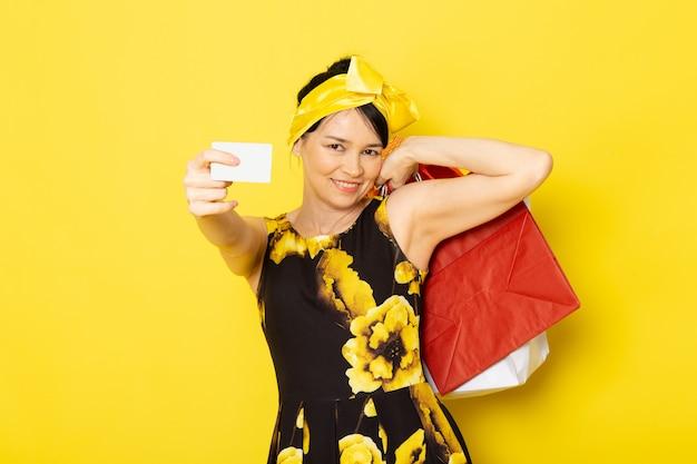 Una giovane signora di vista frontale in vestito progettato dal fiore giallo-nero con la fasciatura gialla sui pacchetti di acquisto della tenuta capa che sorride sul giallo